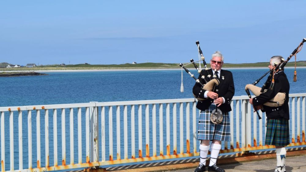 Two pipers play as the cars came down and onto the ferry