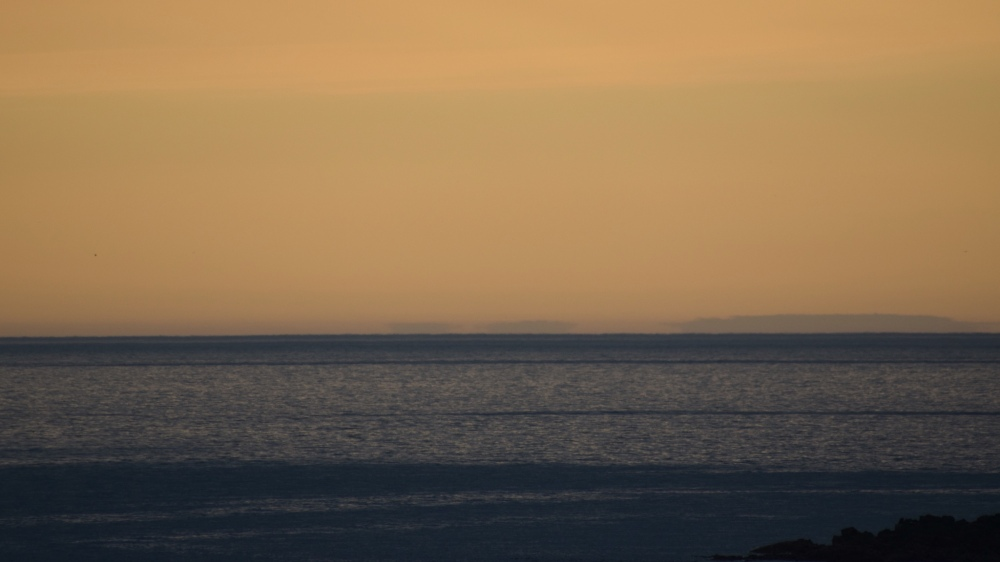 The sun sets over Tiree taken from Colonsay