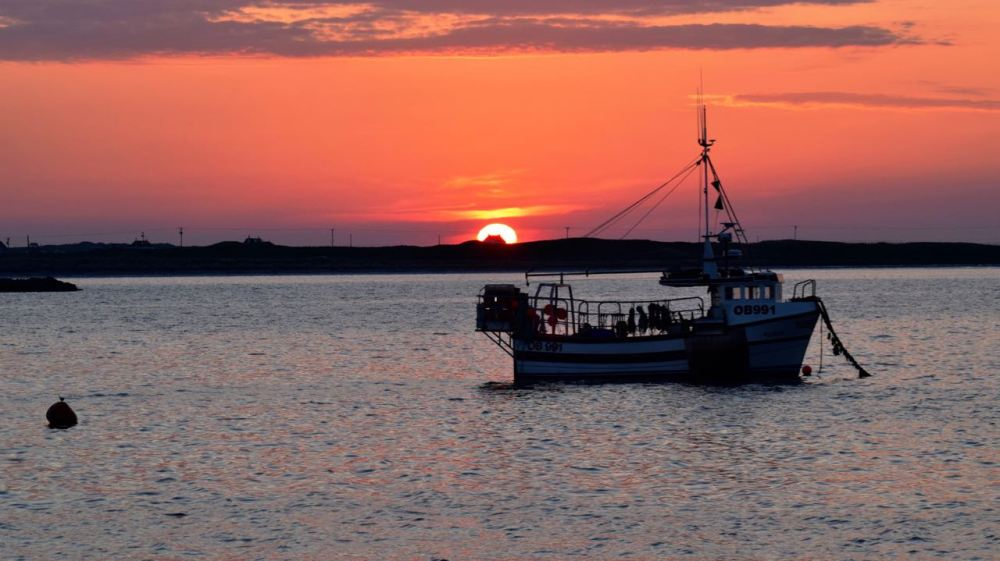Sunset over Gott Bay and the fishing vessel Atlantis