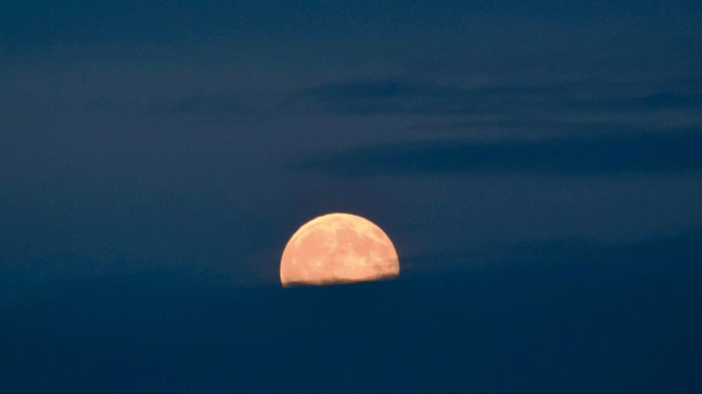 Full Moon cut in half by cloud cover, just before it completely disappeared.