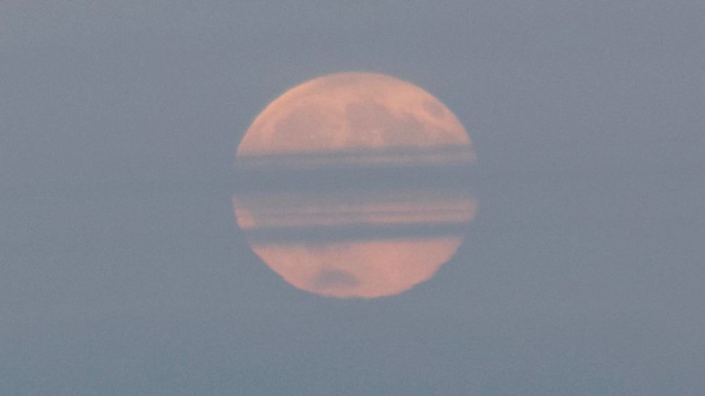Strawberry Moon low in the sky - some cloud cover