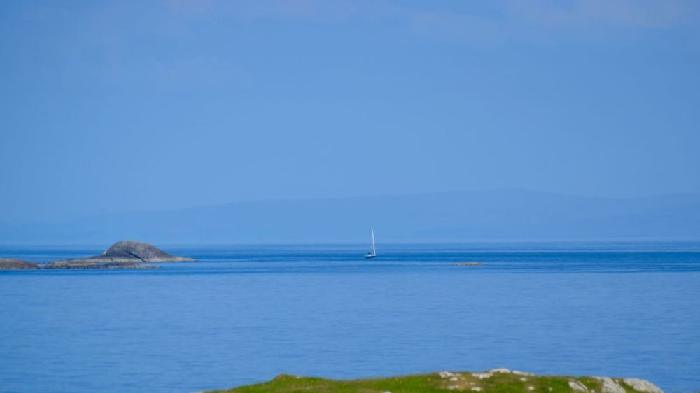 A lone yacht sails towards Gott Bay