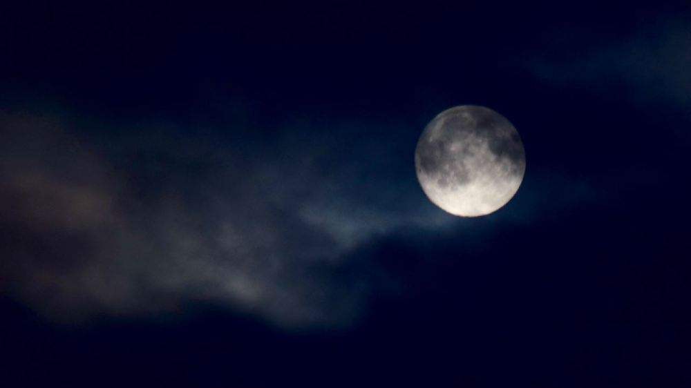 The Moon dancing in and out of the clouds