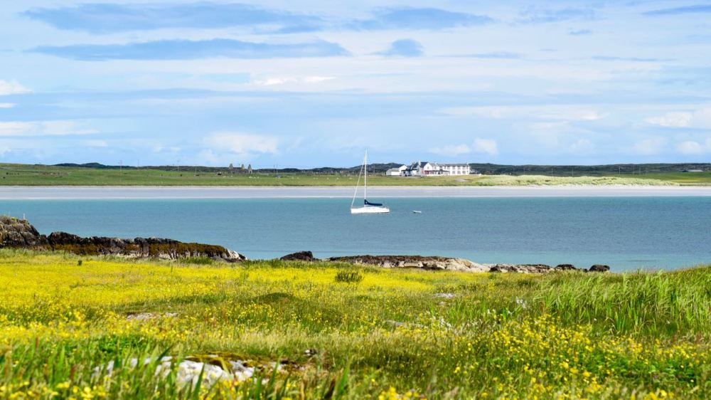 A yacht lies at anchor in Gott Bay on a day of sunshine and showers