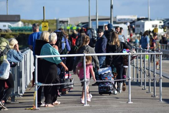 Foot passengers make their way up the pier