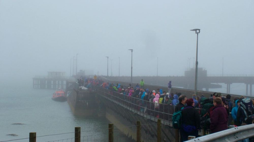 The waiting crowd snakes down the pier approach