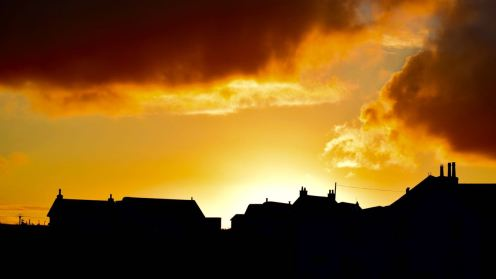 Houses in silhouette against the backdrop of the setting sun