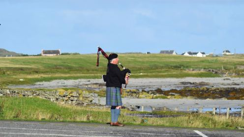 A lone piper - from the ship's entertainment team