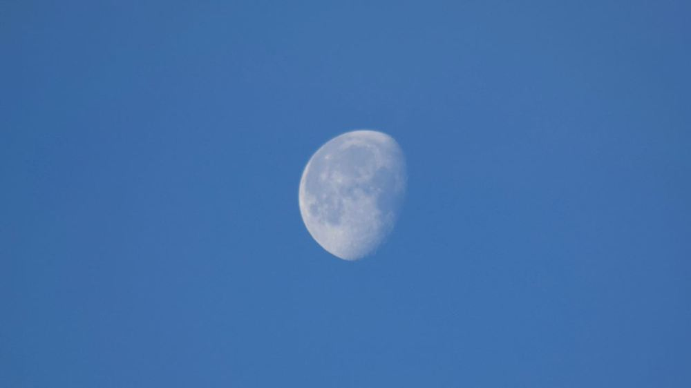 The sun is over the horizon but the moon is still clearly visible to the north-west