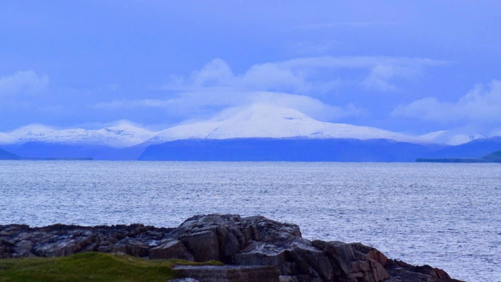 Dusk view of snow capped Ben More on Mull from Tiree's Pier