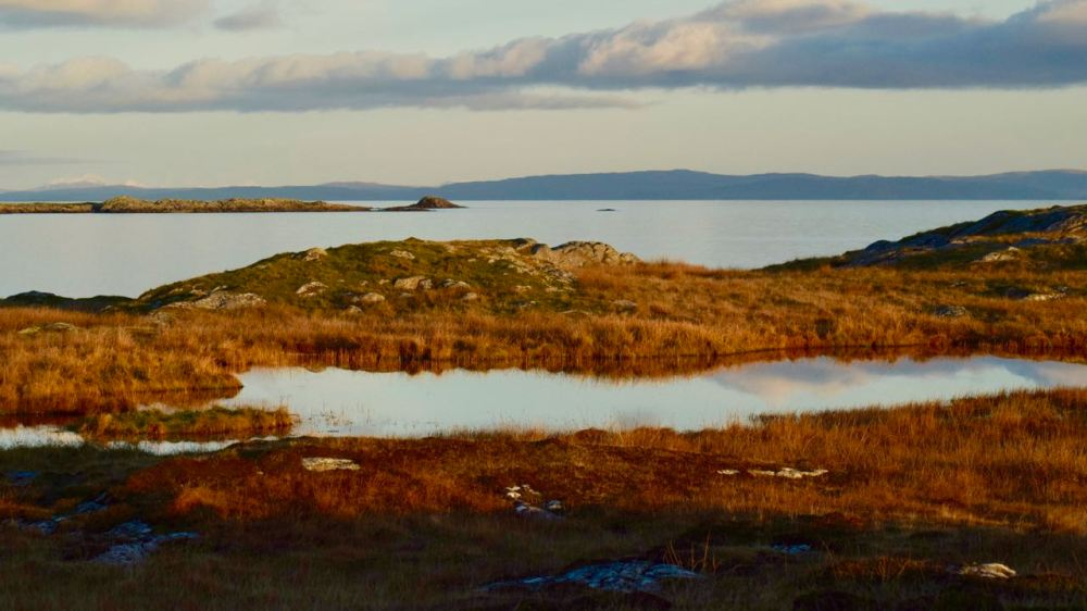 A lochen on the Scarinish Headland looking out across the Passage of Tiree to more distant mountains