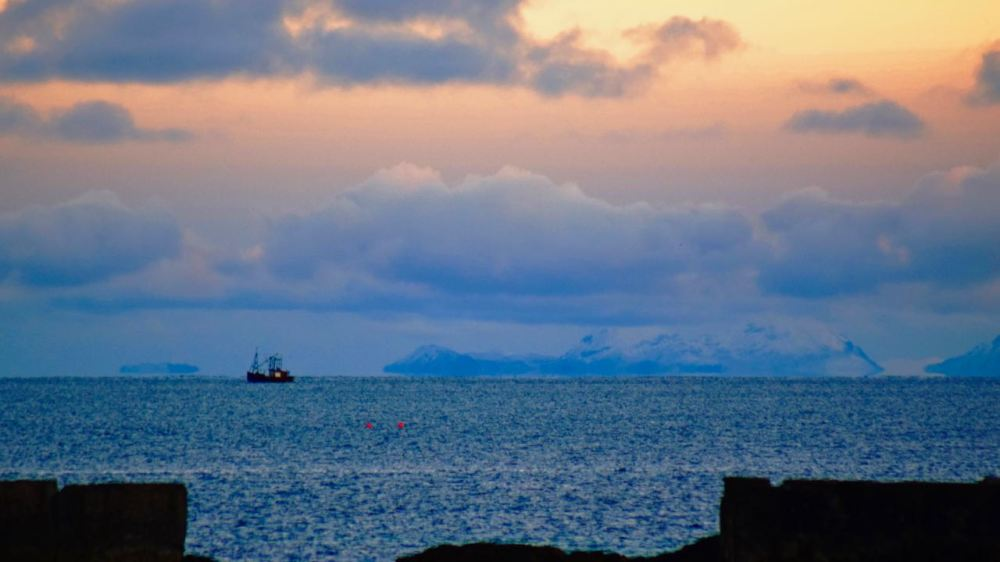 A fishing boat with the Paps of Jura in the background