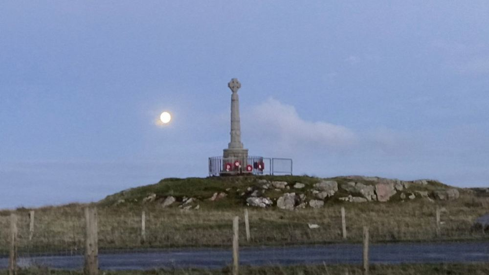 The moon appears behind the Memorial, Pier Road