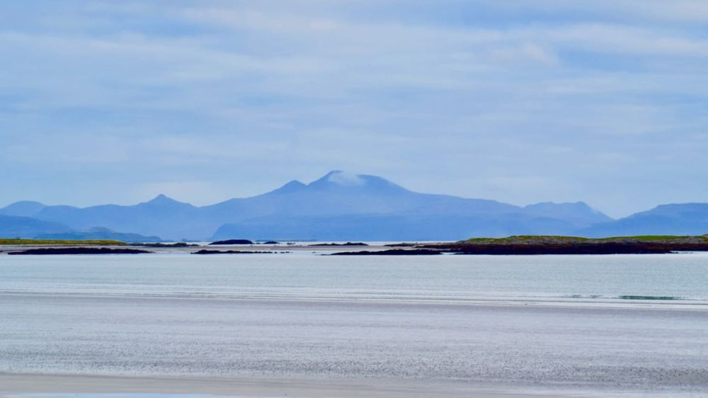 A view across the calm waters of Gott Bay towards Ben More on Mull