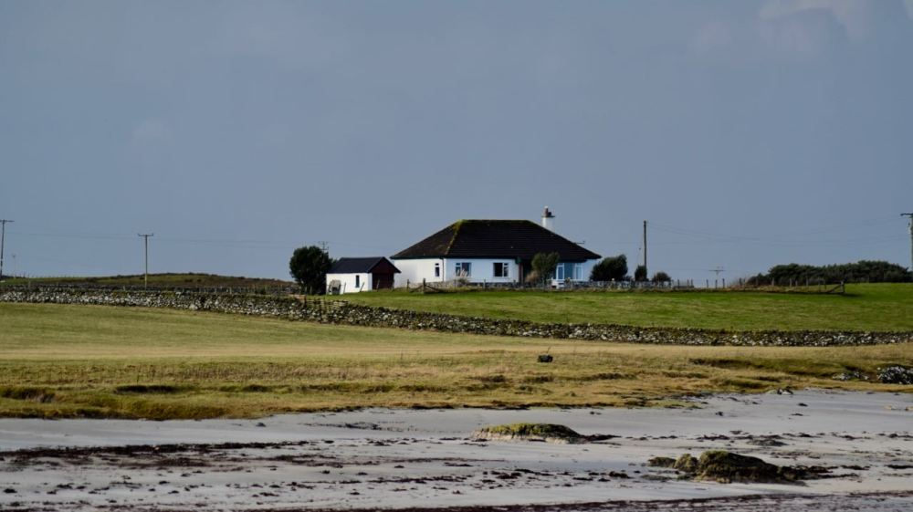 The Church of Scotland Manse looks onto Gott Bay. Today it is under a dark threatening sky.