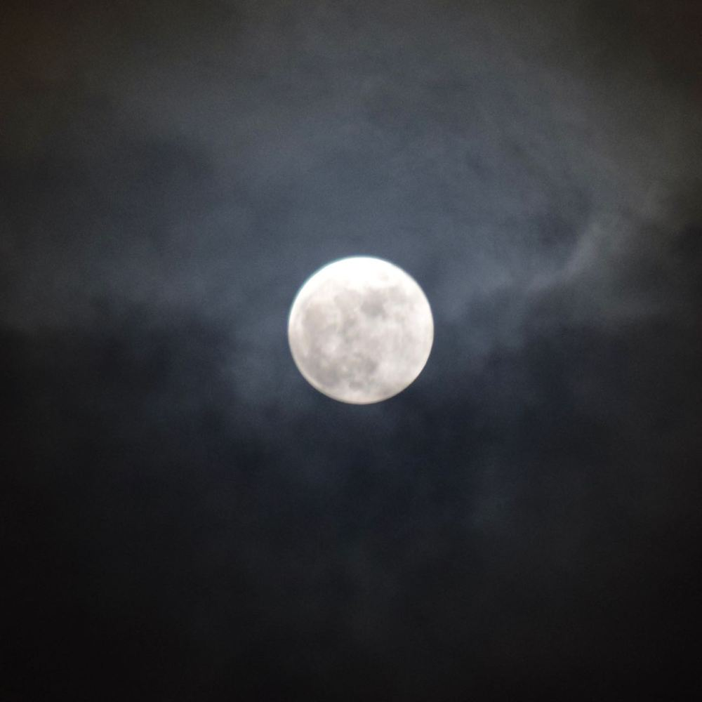 The snow moon partly shrouded by cloud