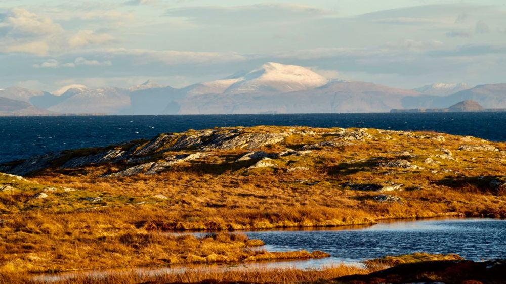 The late afternoon sun reaching across the Passage of Tiree to Ben More