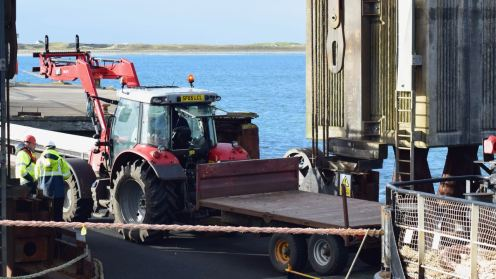 An tractor rolls off the ramp