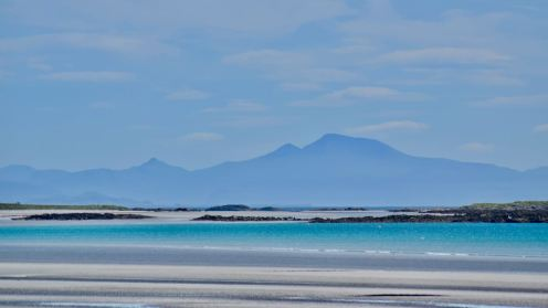 Looking across the white sands and azure waters of Gott Bay to Ben More on the Isle of Mull