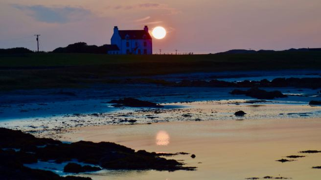 The sun setting behind Glebe House, Gott Bay, Tiree