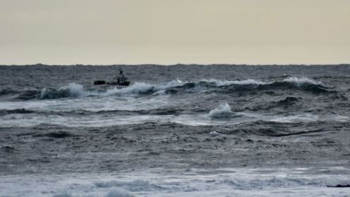 A fishing boat beyond the breakers