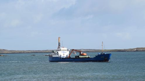 Fishing boat through the MV Burhou's gap/crane