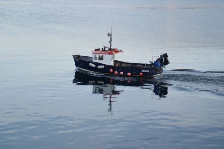 A fishing boat mirrored in the calm waters of Oban Bay