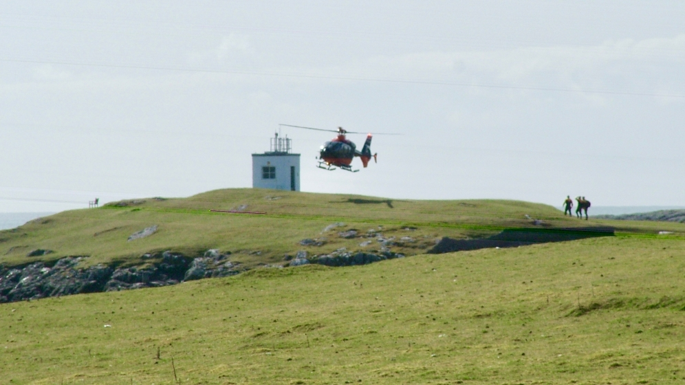 Te helicopter from Pharos touches down by the lighthouse at Scarinish harbour